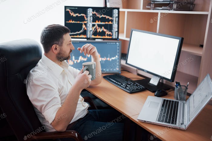 Junger Geschäftsmann sitzt im Büro am Tisch, arbeitet am Computer mit vielen Monitoren, Diagramme