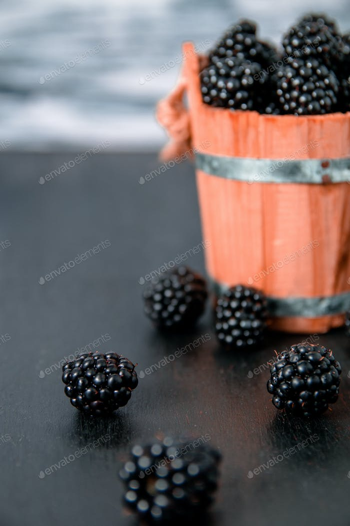 Black raspberries in a wooden basket and on   table. Copy space. Close up.