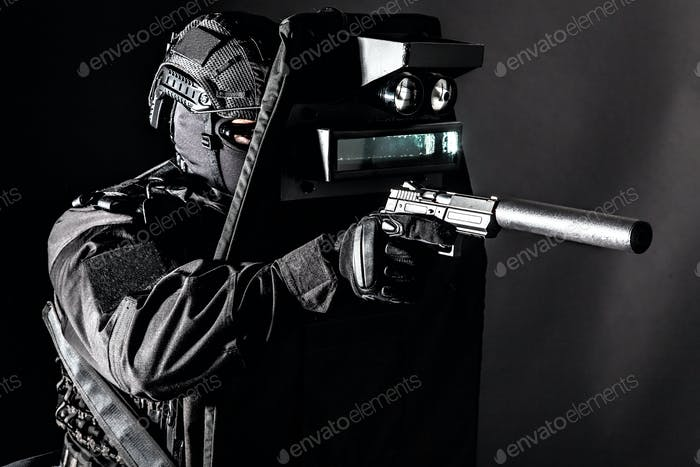 Armed SWAT fighter hiding behind ballistic shield