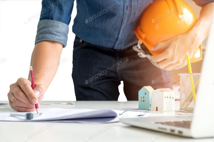 Architect holds a safety hat,using a pencil on paper.
