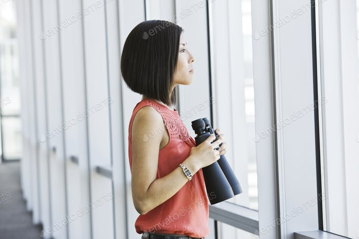 Asian business woman at a business lobby window holding binoculars.