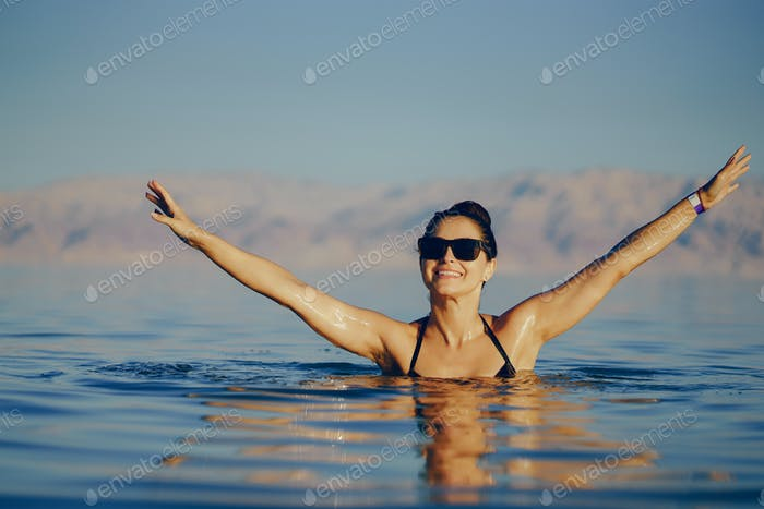 brunette girl swimming in the dead sea