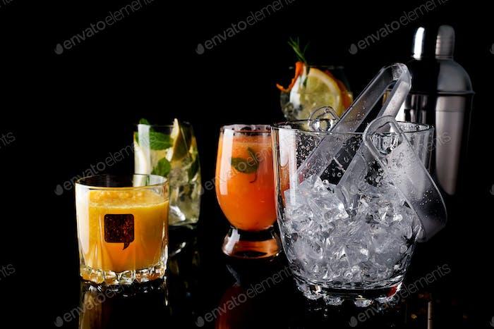 Glas-Eiskübel und verschiedene Cocktails in Glas mit Bar-Zubehör isoliert auf schwarz