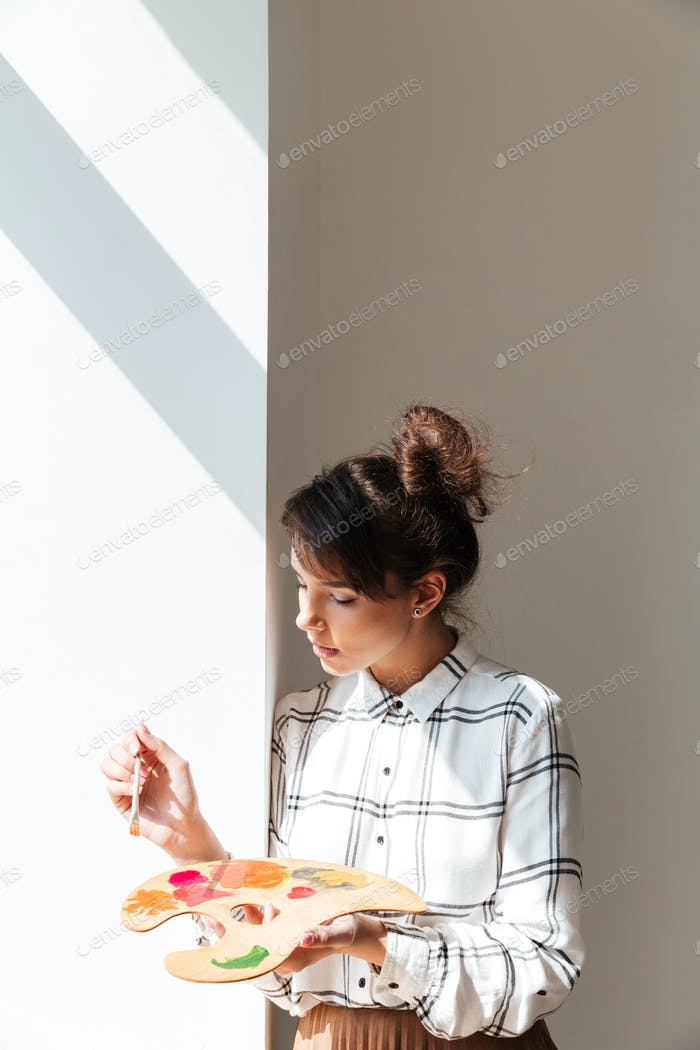 Woman artist holding palette while standing in studio