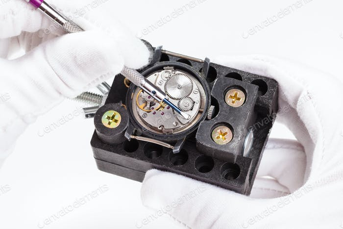 repairing of wristwatch with screwdriver close up