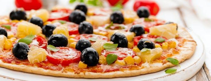 Pizza mit Tomaten, Mozzarella-Käse, Oliven, Mais und Basilikum. Traditionelle italienische Küche. Banner