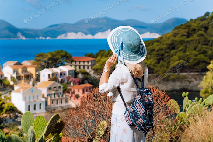 Tourist woman with blue sunhat, white clothes and travel backpack admire view of colorful tranquil