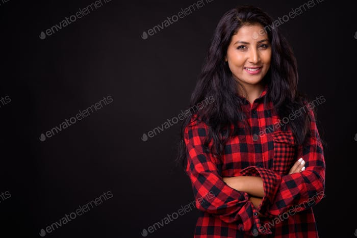 Portrait of happy young beautiful Indian hipster woman smiling with arms crossed