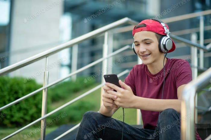 Young man listen to the music in a big earphones, in the street.