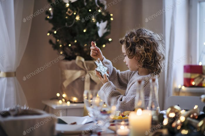 Cheerful small girl sitting indoors at Christmas, holding ornament.