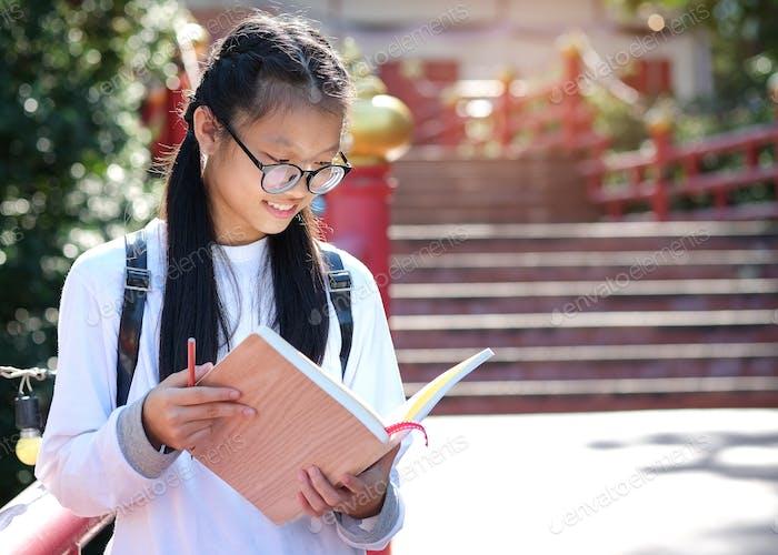 Asian female student standing reading in garden.