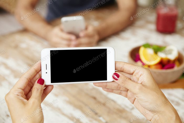 Technology and communication concept. Female hands holding smart phone horizontally, showing blank s