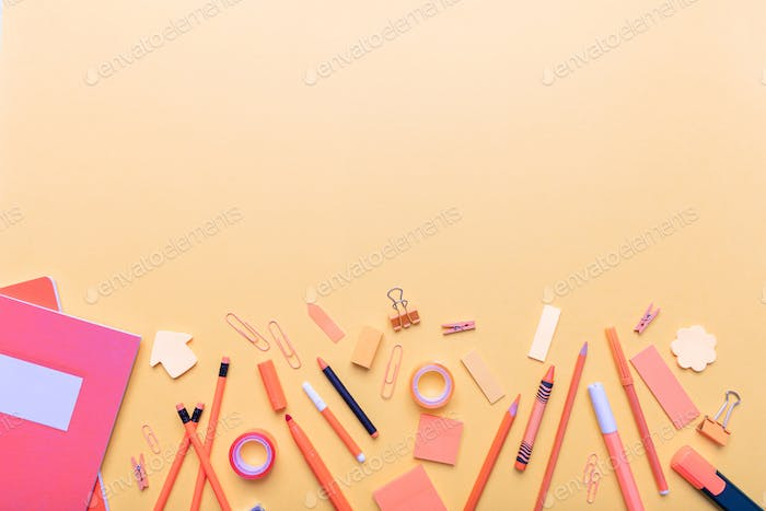 Flat lay of school stationery on orange color background