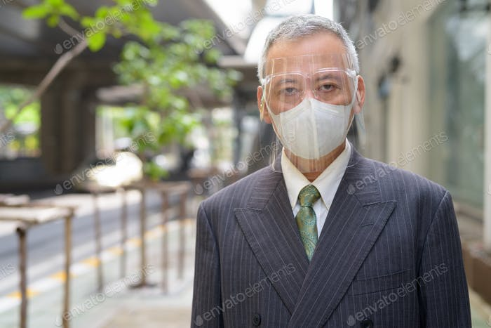 Mature Japanese businessman with mask and face shield in the city