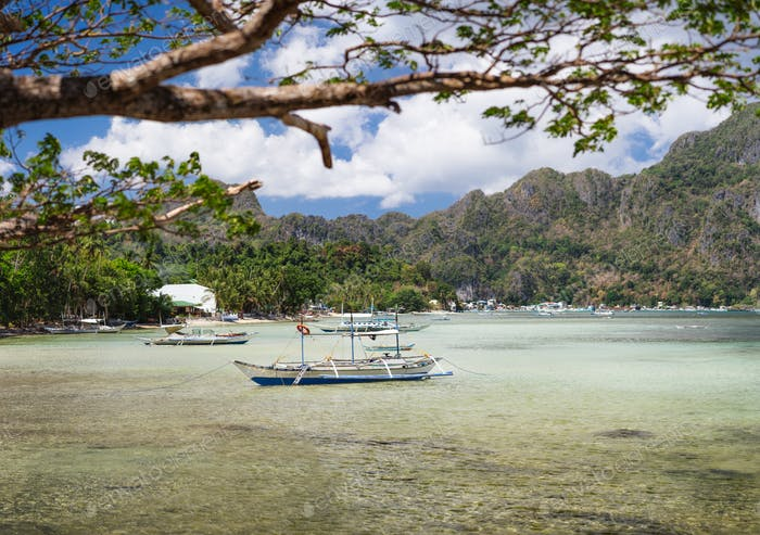 El Nido bay in low tide. Bangka fishing in the shallow water in low tide. Palawan, Philippines