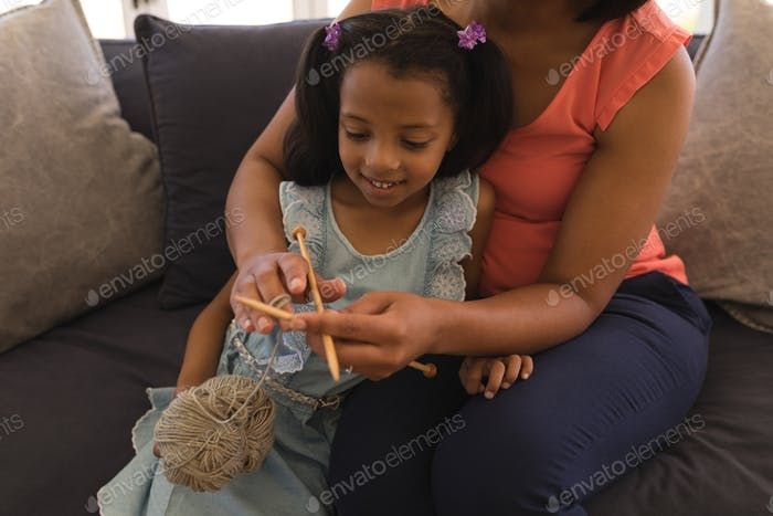 Grandmother teaching her granddaughter how to knitt in living room at home