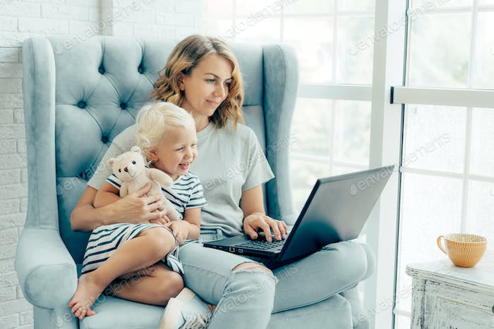 Mom and little daughter are sitting on an armchair with a laptop.
