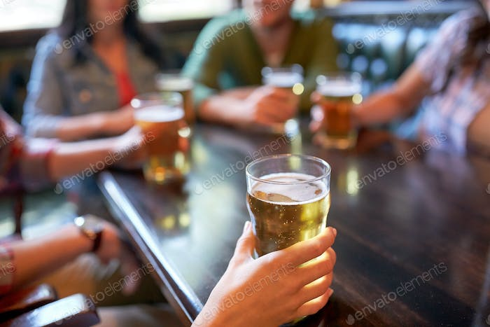 friends drinking beer at bar or pub