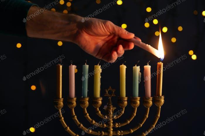 Teilansicht eines Mannes, der Kerzen in Menora auf schwarzem Hintergrund mit Bokeh-Lichtern auf Hanukkah anzündet
