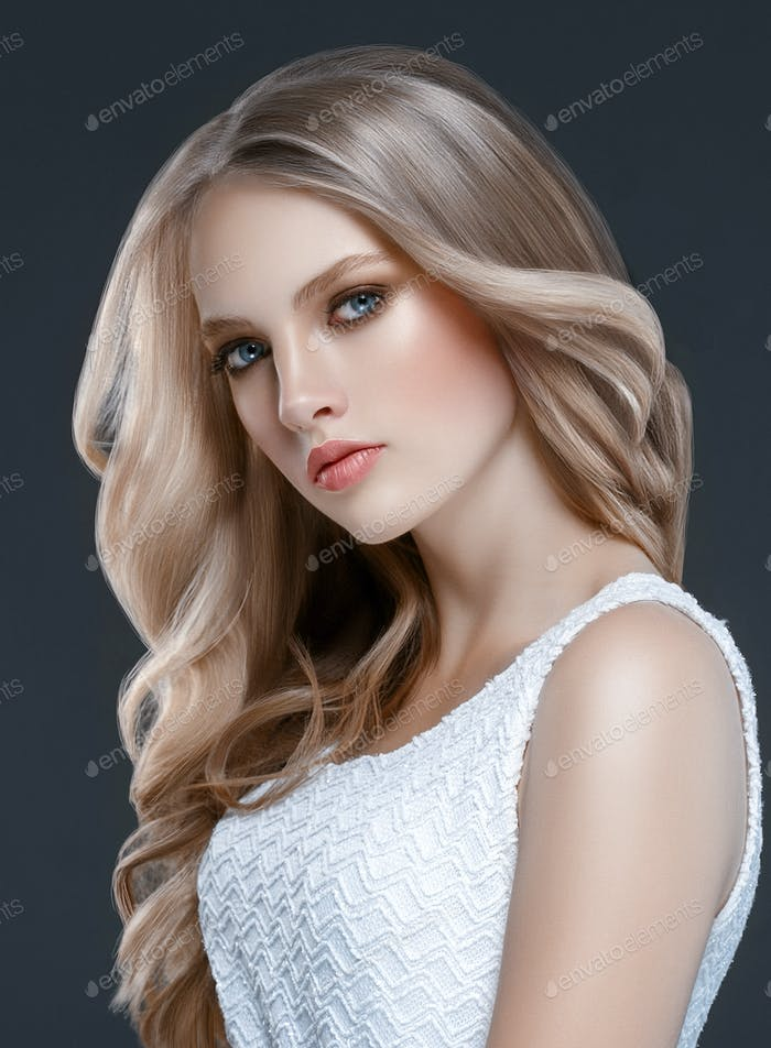 Young beautiful girl with long wavy hair. Blonde model with hairstyle over black background