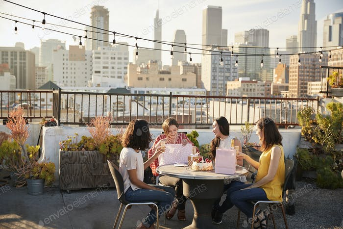 Female Friends Celebrating Birthday On Rooftop Terrace With City Skyline In Background