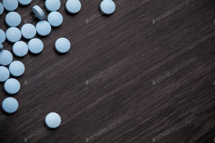 Medication pills in a row against a wood background.