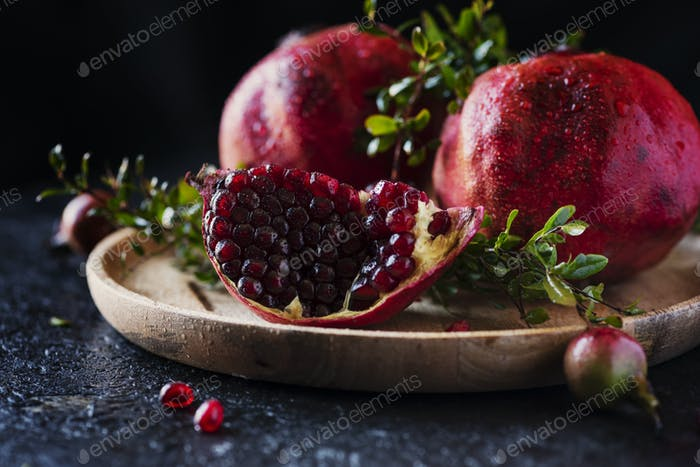 Sweet red pomegranate with green leaves