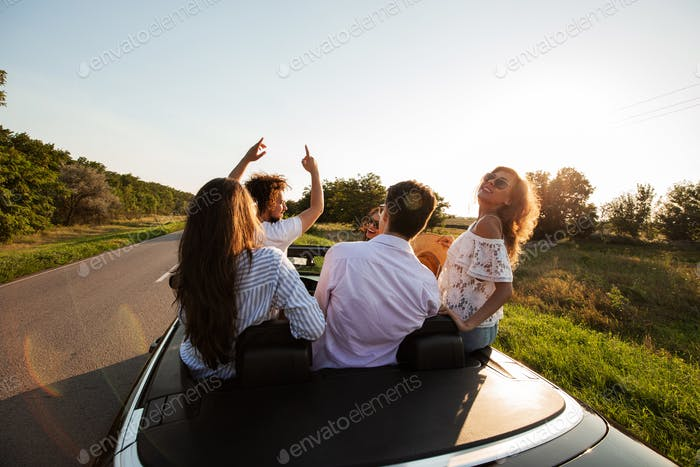 Funny company of happy young girls and guys are sitting in a black cabriolet road on a sunny day