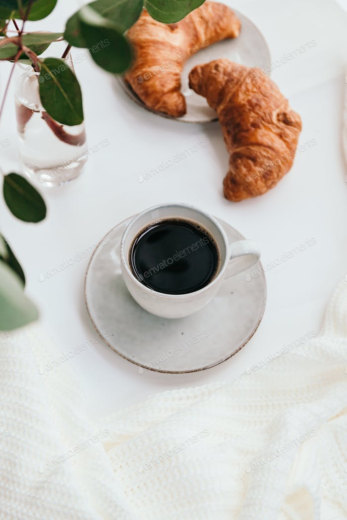 Cup of black coffee with croissant on white  table