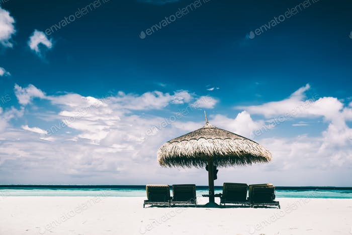 Straw umbrella and sunbeds on a sandy beach