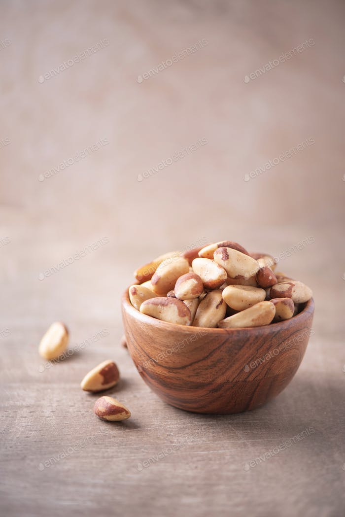 Brazil nuts in wooden bowl on wood textured background. Copy space. Superfood, vegan, vegetarian