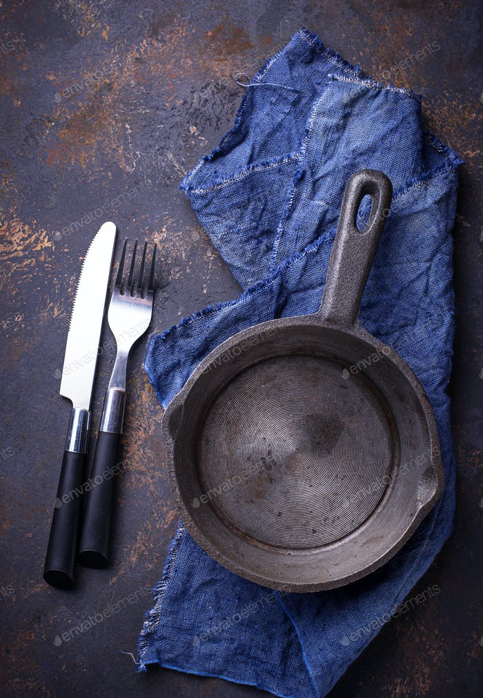 Empty cast iron fried pan with cutlery