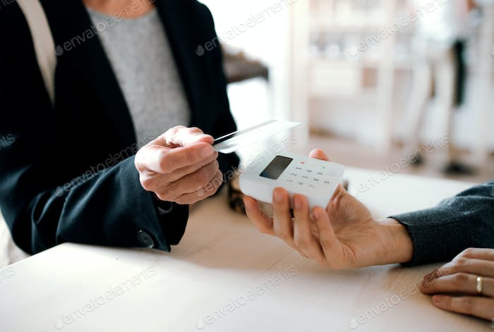 A midsection of customer and shop assistant making contactless payment in a shop.