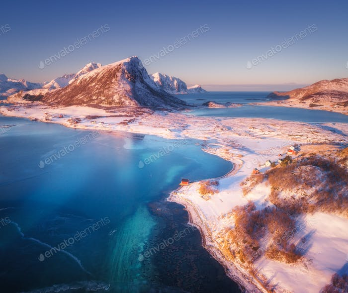 Aerial view of snow covered mountains, houses, clear water
