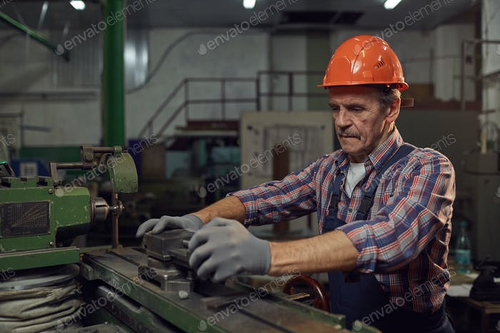Manual worker cutting the metal