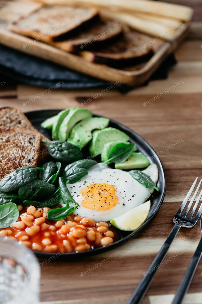 Healthy breakfast with fried egg, avocado, toasts, beans and fresh spinach