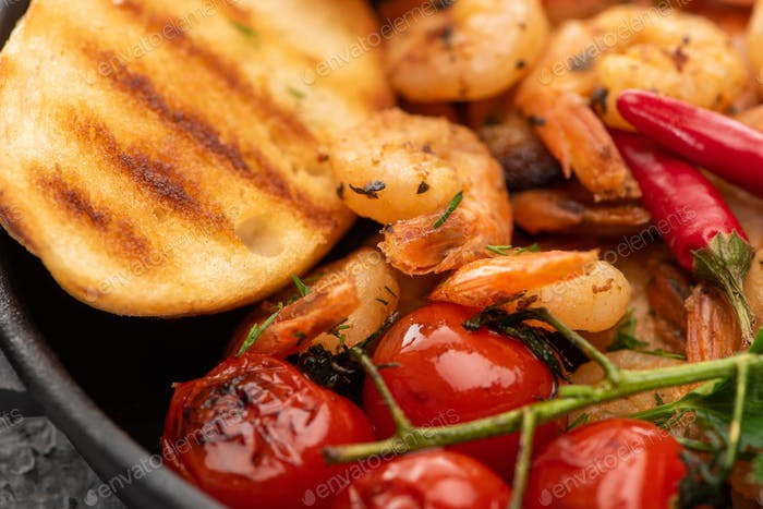 close up view of fried shrimps with grilled bread, tomatoes, chili peppers