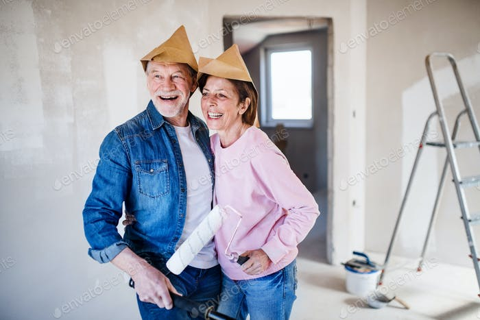 Senior couple painting walls in new home, laughing. Relocation concept
