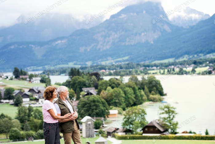 A senior pensioner couple hikers standing in nature, resting.