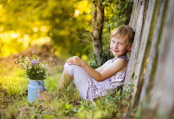 Niedliches kleines Mädchen mit Blumen lachen