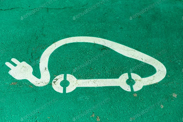 Car charging symbol painted on asphalt.