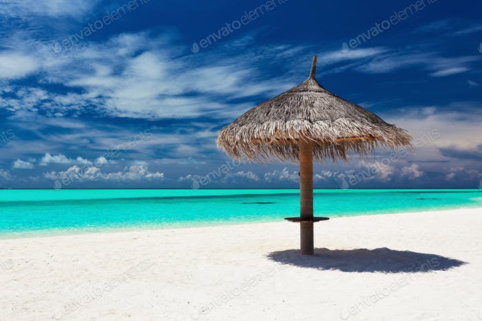 Single tropical beach umbrella on romantic white beach