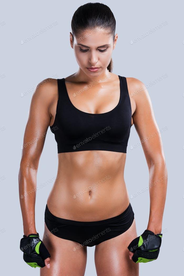 Energie in ihr. Schöne junge sportliche Frau mit perfektem Körper steht vor grauem Hintergrund