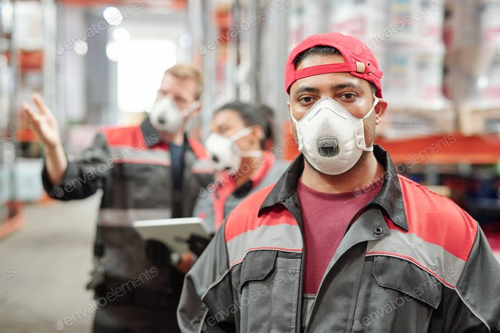 Middle aged Latino man in workwear and protective respirator looking at you