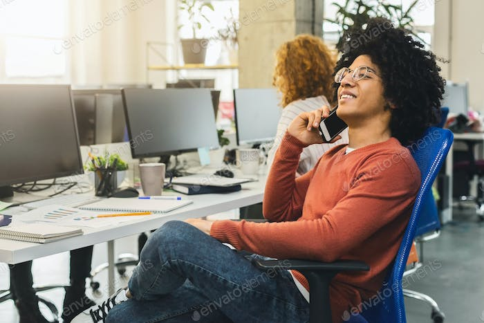 Young african american man talking on phone in modern coworking