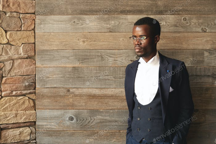 Graceful African American gentleman standing indoors in daylight on wooden background and looking aw