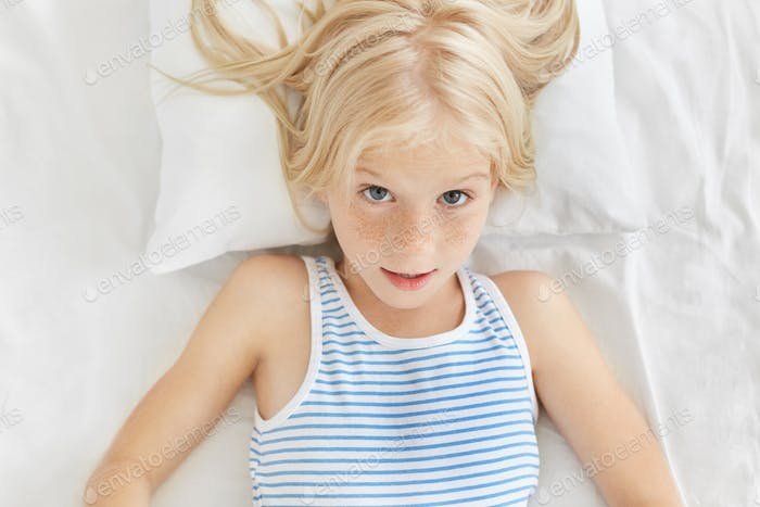Portrait of cute blonde girl wearing sailor t-shirt, looking surprisedly into camera, awaking in mor