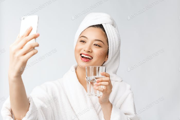 Healthy young beautiful woman drinking water, beauty face natural makeup with holding mobile phone