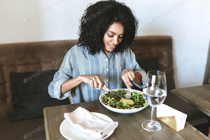 Beautiful girl with dark curly hair sitting at cafe and eating salad