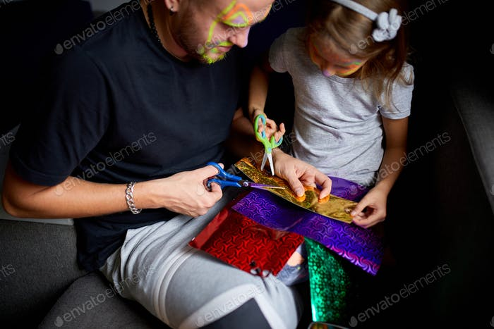 Daughter and father having fun making craft together at home on the sofa